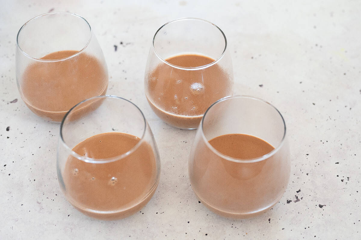 Four glasses filled with chocolate panna cotta liquid