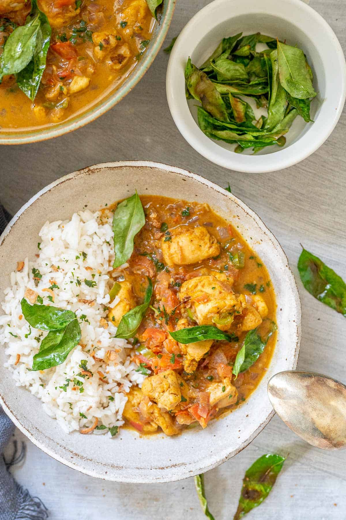 a bowl of chicken kerala curry with curry leaves