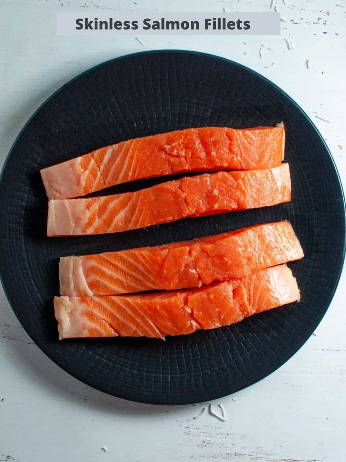 four skinless salmon fillets on a black plate