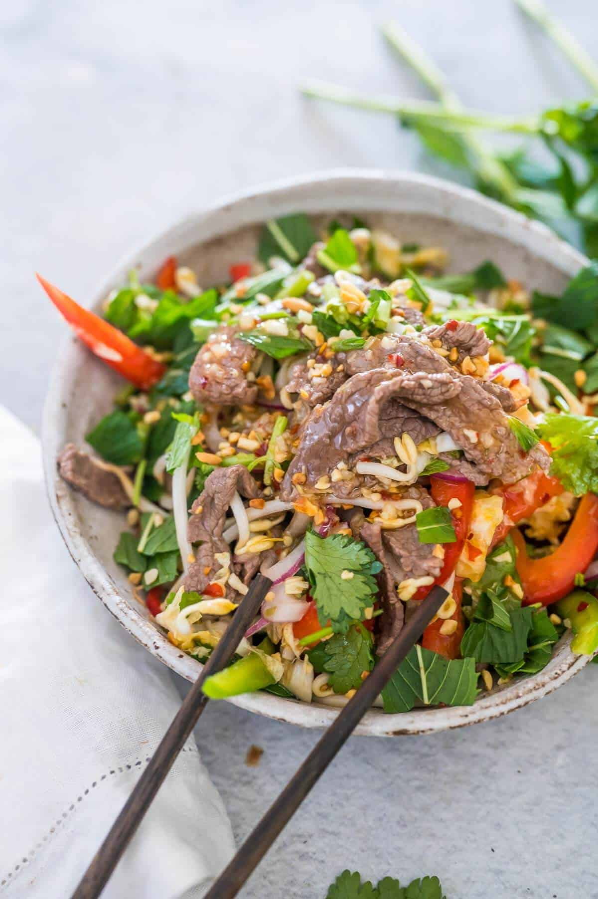 a bowl of vietnamese beef salad with dressing and peanuts on top