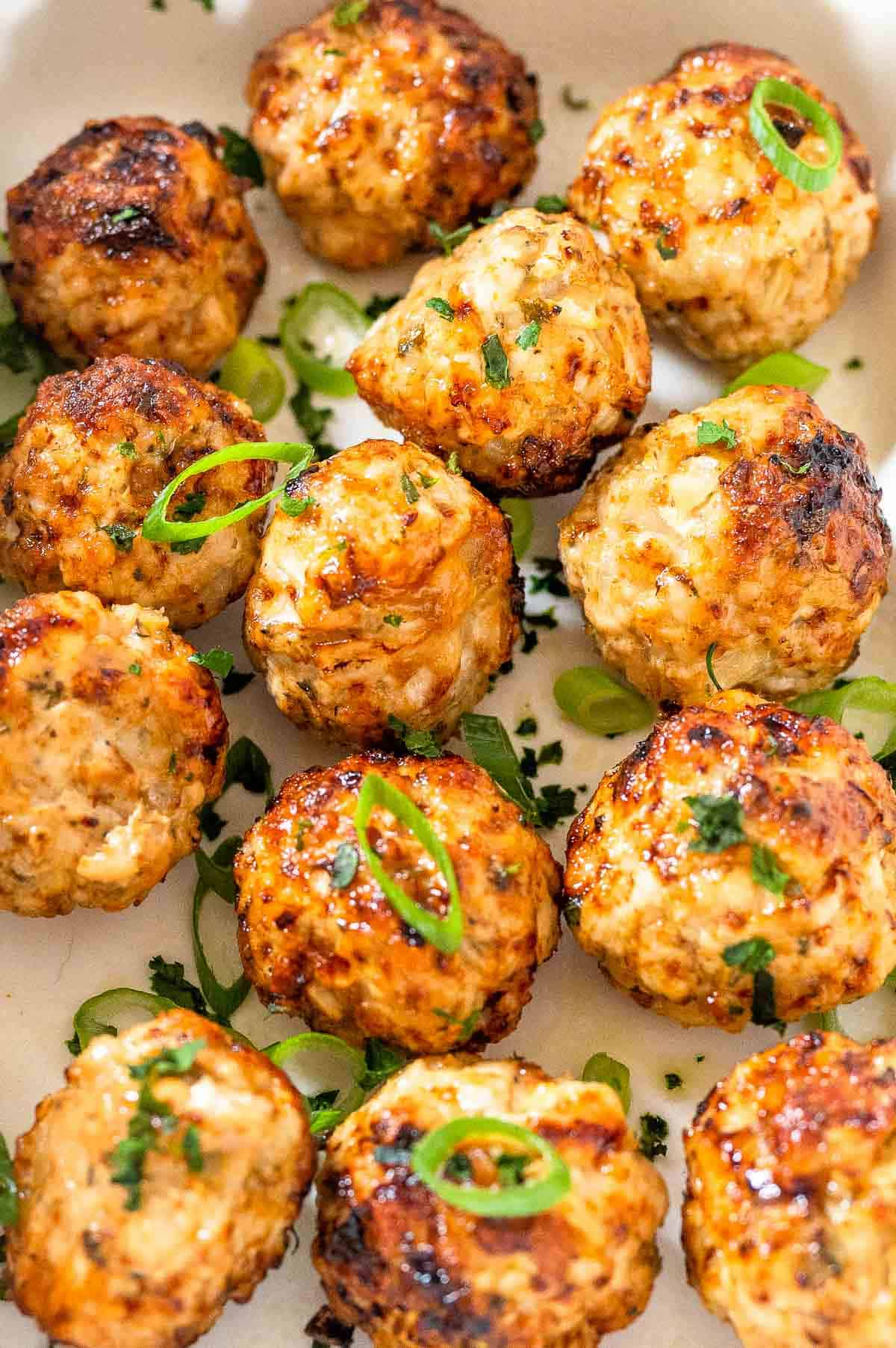 cooked air fryer turkey meatballs garnished with green onions and herbs