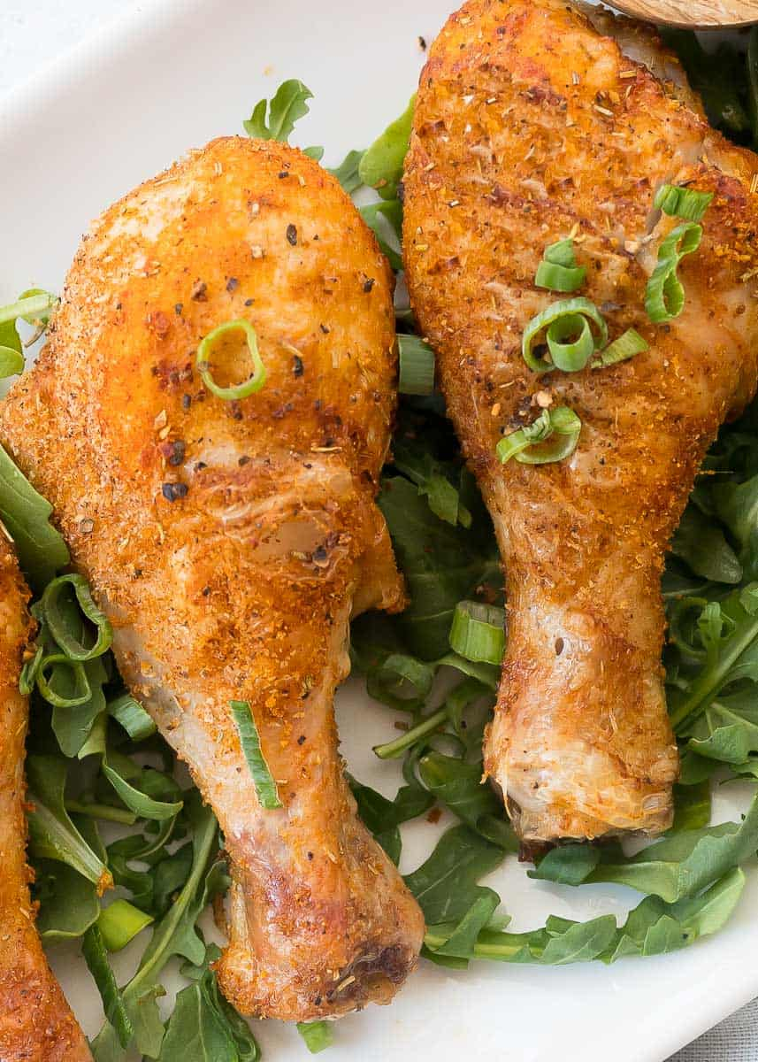 two cooked chicken drumsticks on a plate