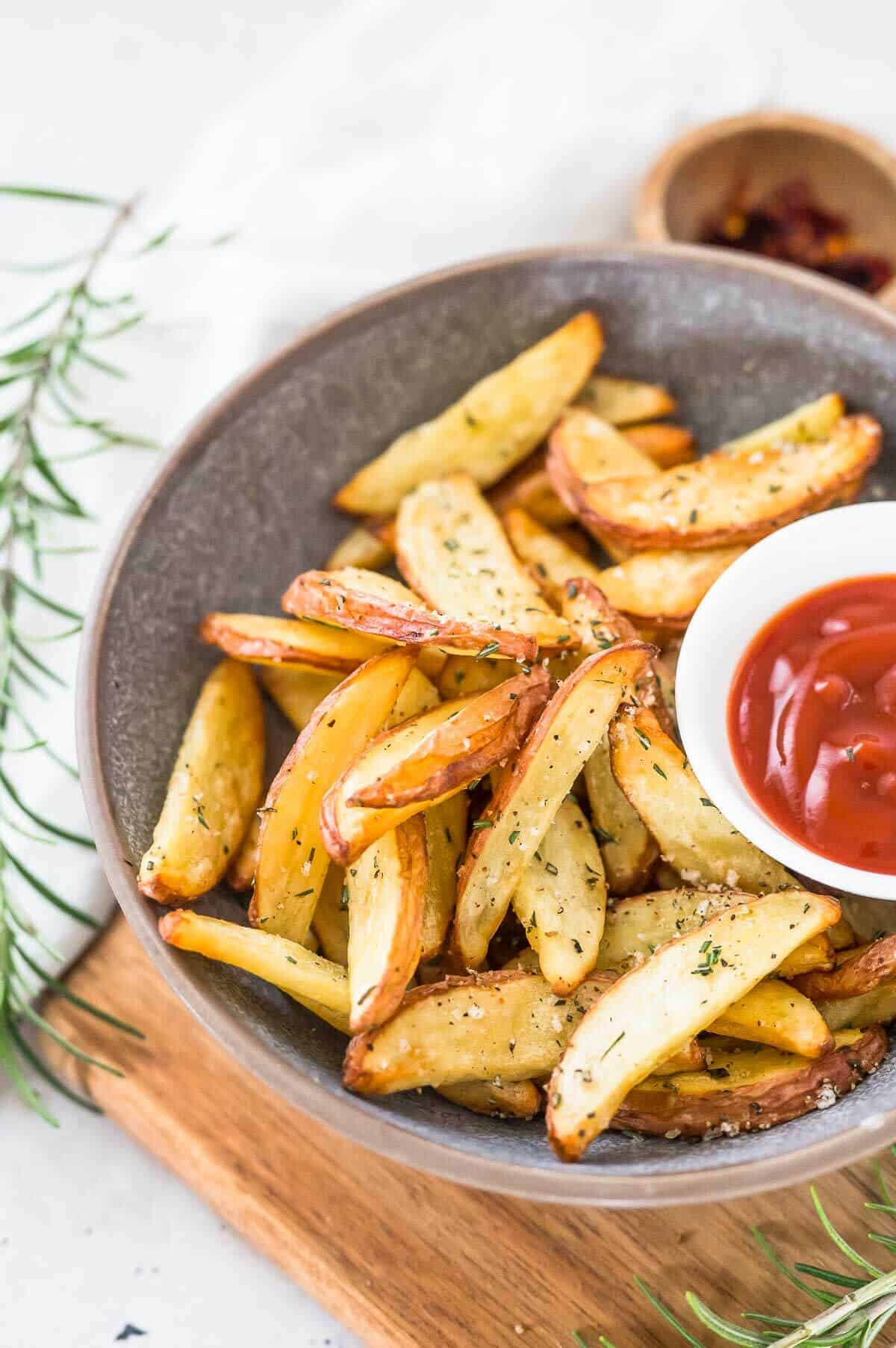 a bowl of potato wedges with a small bowl of sauce on the sauce