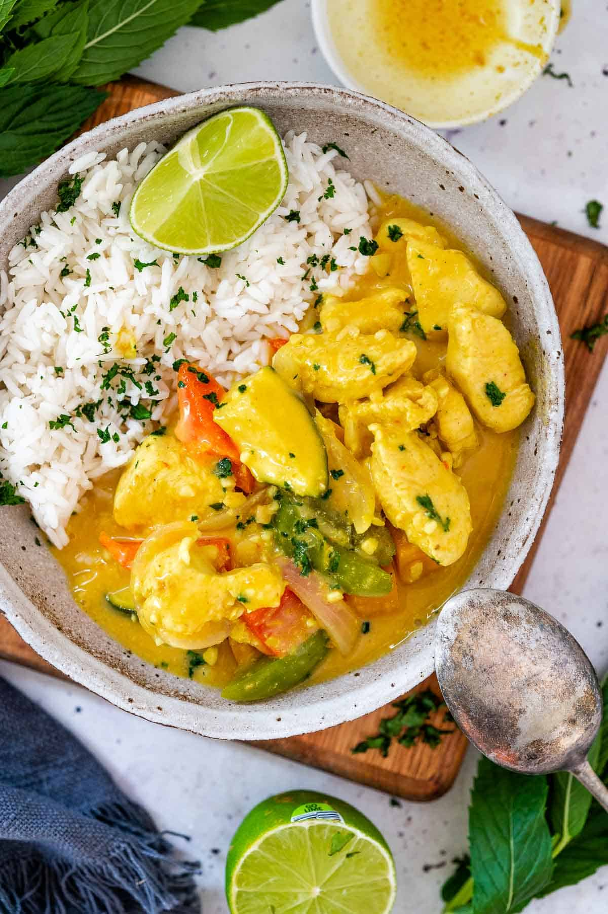 a bowl of creamy chicken curry with rice and lime wedge