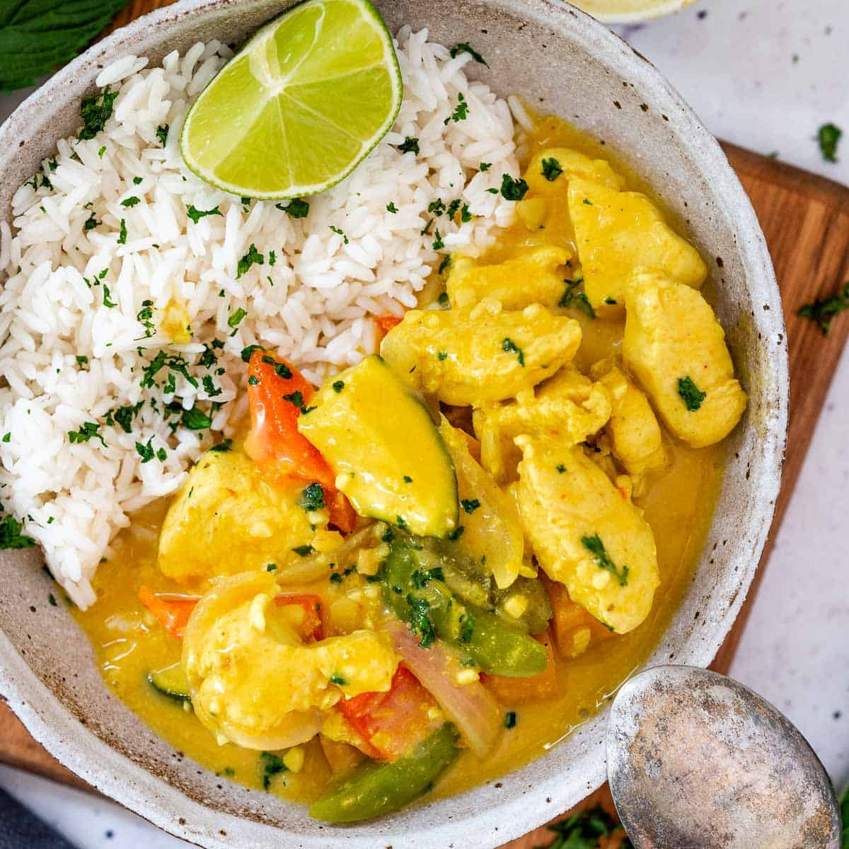 a bowl of thick and creamy yellow coconut chicken curry ready to serve with spoon