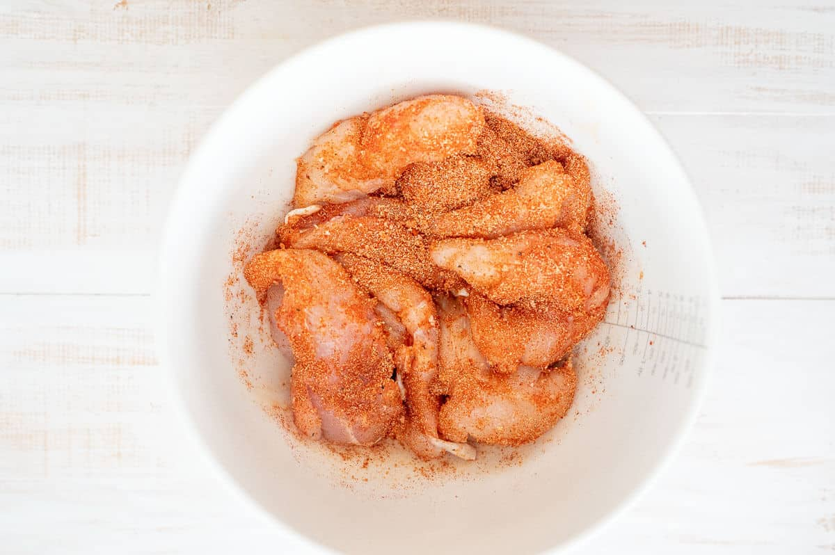 uncoked chicken tenders with seasoning in a white bowl