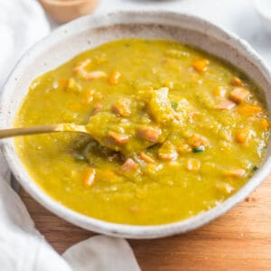 a bowl of split pea soup with bacon with spoon in