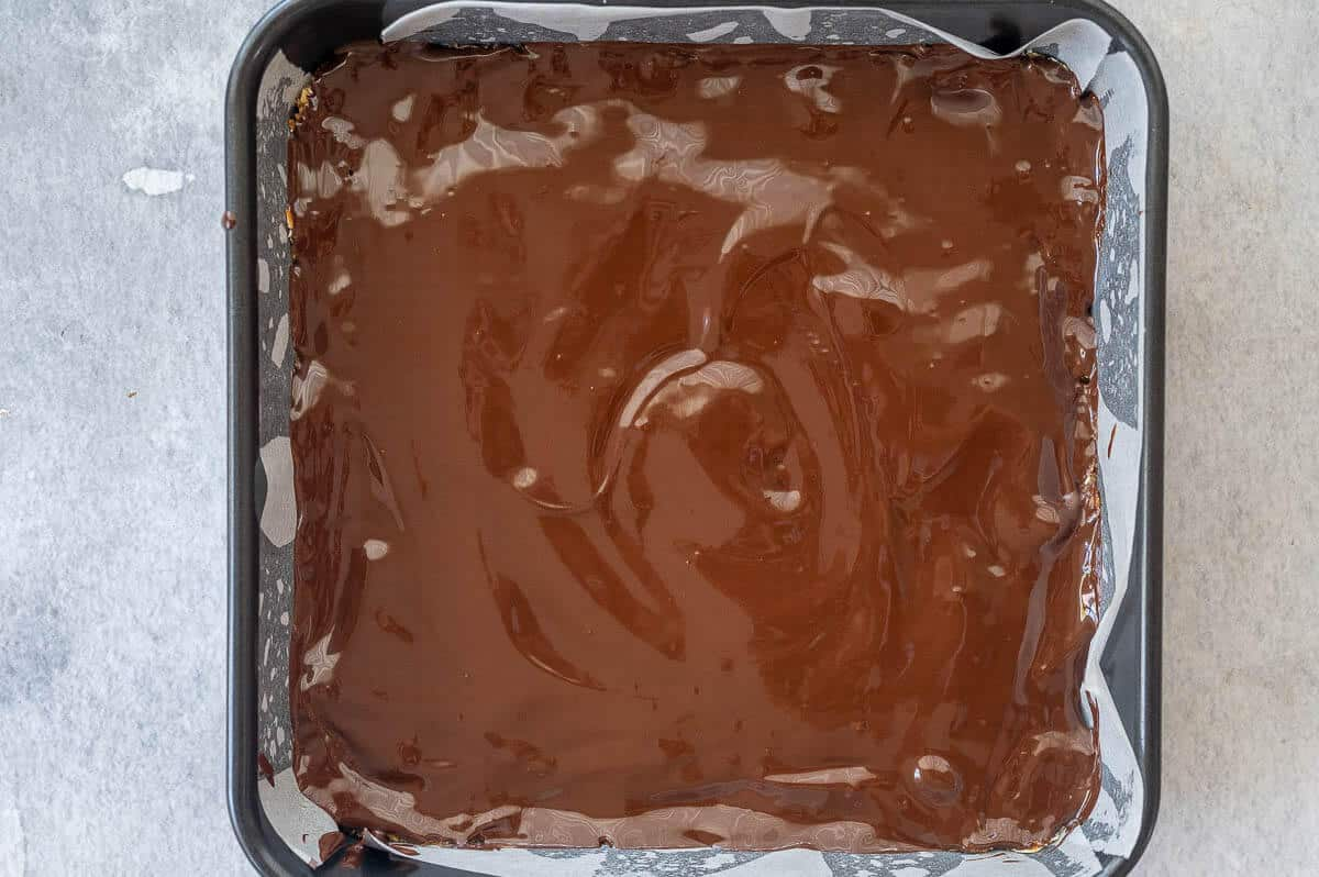 peanut butter bar mixture in tin with melted chocolate poured over