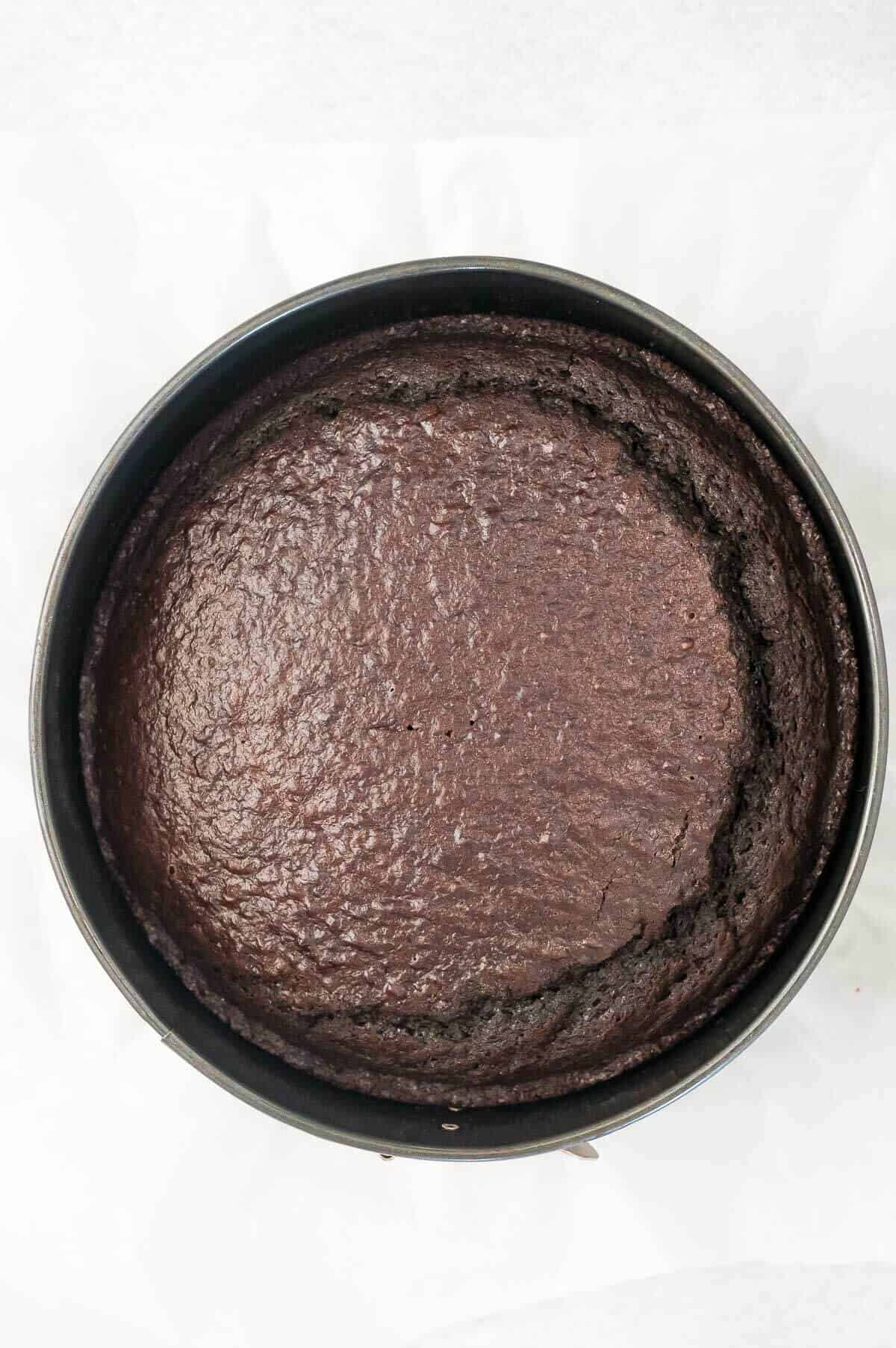 baked chocolate cake in a round cake tin