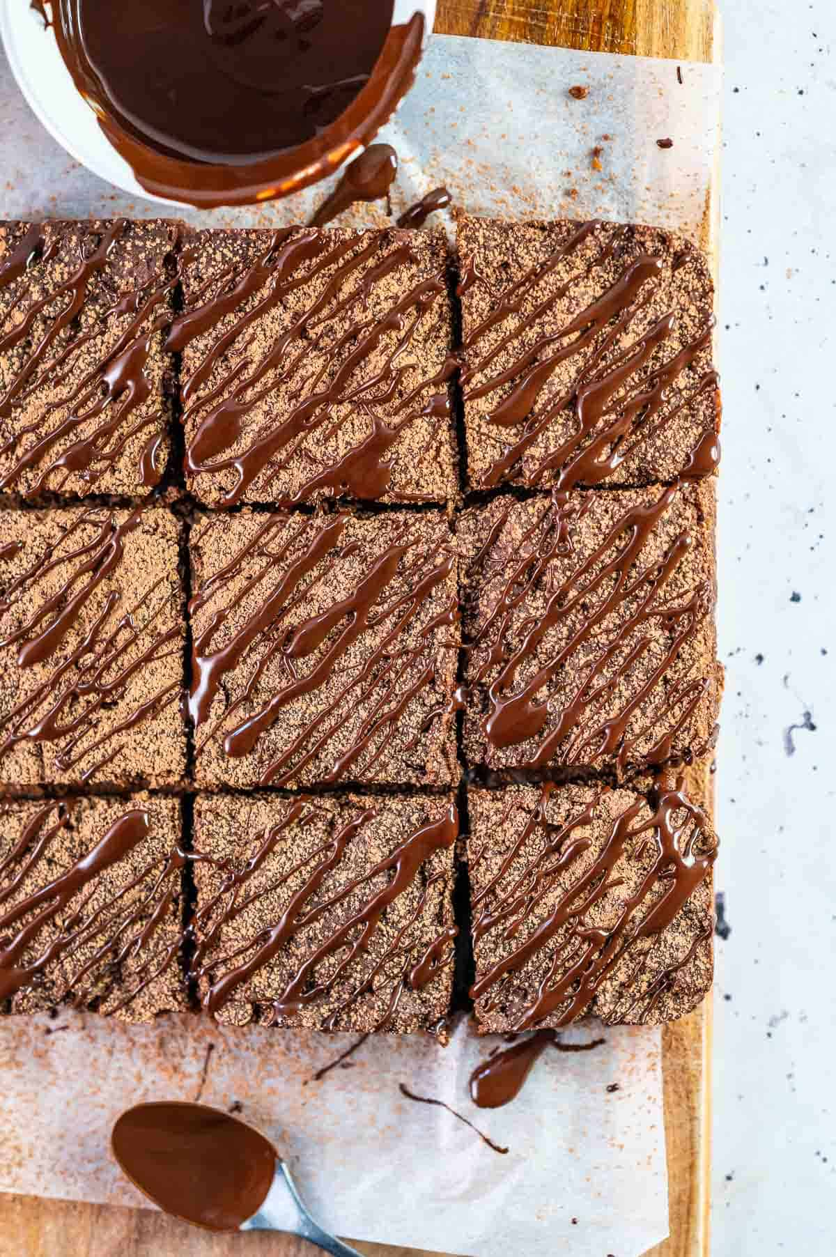 nine brownies on a board drizzled with chocolate
