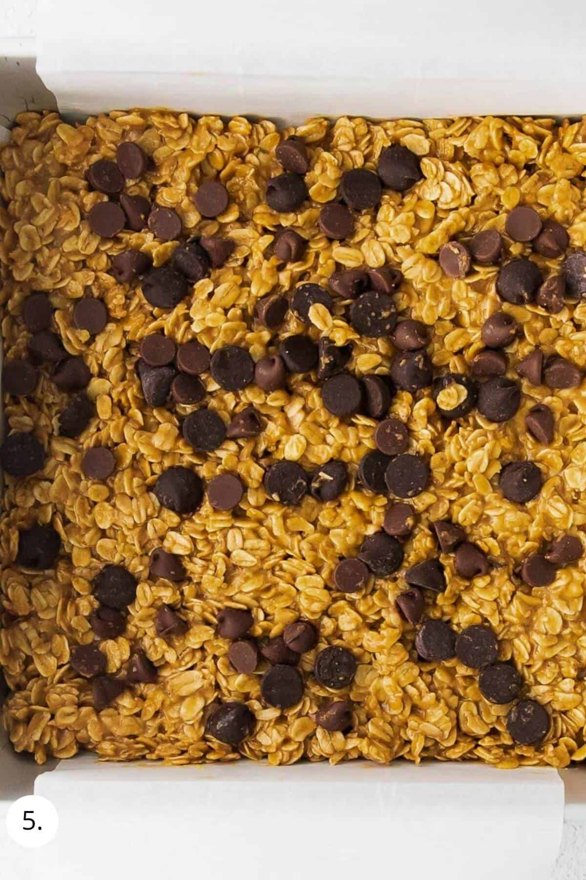 granola bar mixture in a pan with chocolate chips